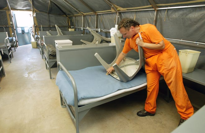 An inmate cleans chairs inside her tent at the Arizona State Prison Complex-Perryville, Wednesday, August 27, 2003. Overcrowding has necessitated the use of tents.