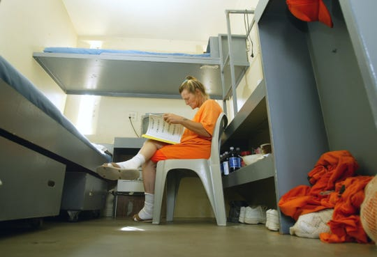 An inmate reads inside her cell at the Arizona State Prison Complex-Perryville, Wednesday, August 27, 2003. Overcrowding has necessitated double bunking and the use of tents.