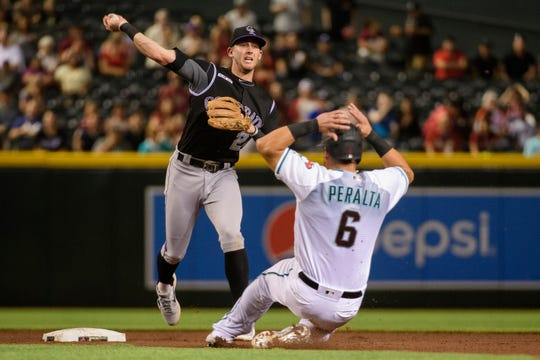 Ryan McMahon #24 of the Colorado Rockies turns the double play over David Peralta #6 of the Arizona Diamondbacks in the fifth inning of the MLB game at Chase Field on June 18, 2019 in Phoenix, Arizona.