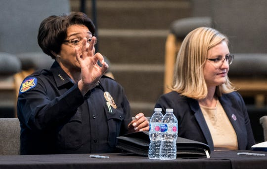 With Phoenix Mayor Kate Gallego to her left, Phoenix Police Chief Jeri Williams gives the OK sign to a friend before the beginning of a public meeting about a controversial viral video, at the Pilgrim Rest Baptist Church in Phoenix, June 18, 2019.