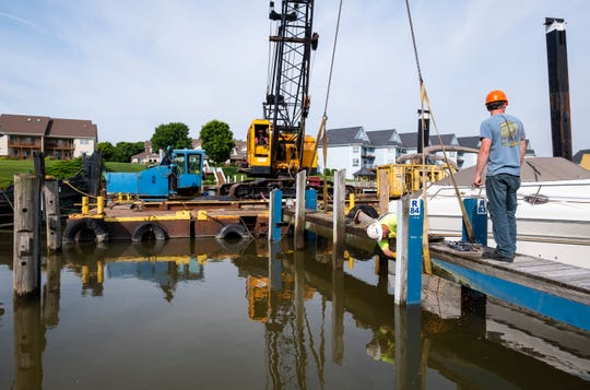 Dean Marine Excavating employees Michael Kinney, right, and Dan Buchanan work to secure a dock while Henry Broaden uses a crane to hold it in place Wednesday, June 19, 2019 at River Street Marina.