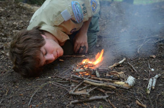 Eagle Scout Ian Boden blows softly to fan a small fire as he builds a campfire at Silver Trails Boy Scout Camp in Jeddo in 2013.