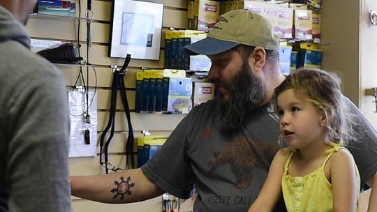 The Feathered Hook fly shop owner, Jonas Price, is used to carrying on multiple conversations at once. Here he is running the cash register in his fly shop while talking to customers and entertaining children.