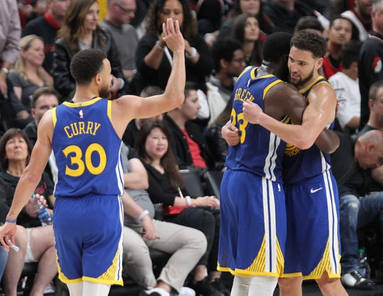 The Warriors Stephen Curry, left, celebrates with Draymond Green and Klay Thompson after Western Conference finals Game 3.