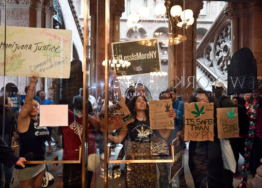 Protesters urging legislators to pass Marijuana legislation holds a signs against the senate lobby doors at the state Capitol Wednesday, June 19, 2019, in Albany, N.Y. (AP Photo/Hans Pennink)