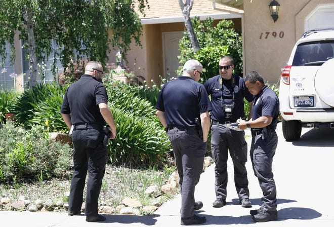 Redding police Investigator Boun Kongkeoviman, right, meets with other officers during their investigation at 1790 Galway Drive in west Redding on Wednesday, June 19, 2019.