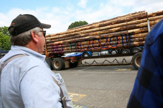 """Logs on the bed of a truck have """"No HB202"""" written on them in front of the Oregon State Capitol in Salem on June 22, 2019. Loggers and truckers protest the bill outside before going in to speak to representatives."""