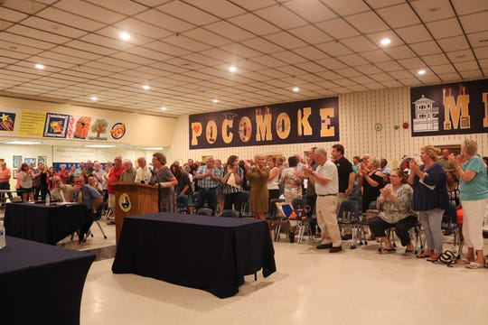Pocomoke City residents stand and clap to show their support for suspended city manager Robert Cowger at Pocomoke Middle School on June 18, 2019.