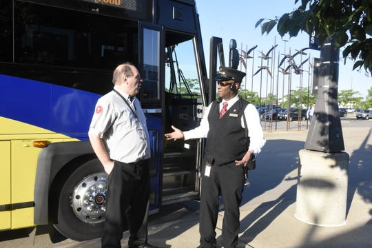 Northstar Link bus driver Adam Ploof (left) and Northstar train conductor Vincent Roberts chat before the train's 7:18 a.m. departure from the Big Lake station on June 18, 2019.