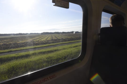 Passengers get views of farms and forests from the top deck of the Northstar commuter train between Big Lake and Minneapolis, Minnesota, on June 18, 2019.