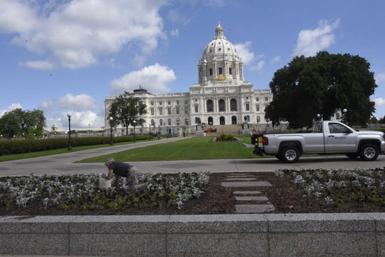 A state employee works in the flower beds in front of the Minnesota Capitol in St. Paul on June 19, 2019.