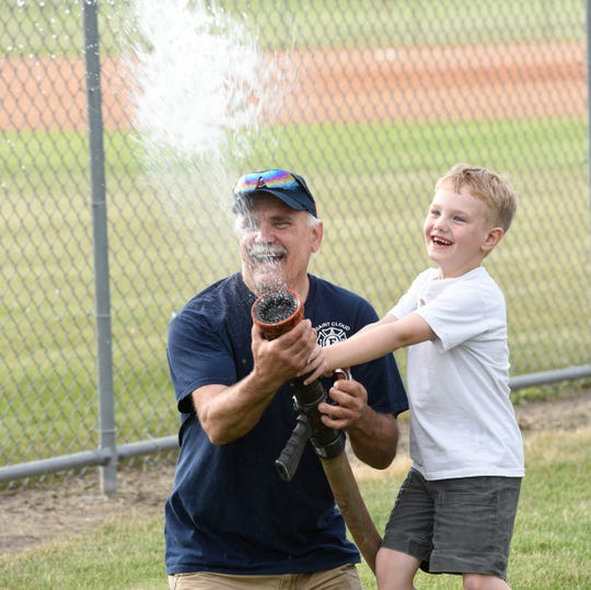 Brian Cash lets Anthony Kapinos play with a fire truck hose after a Miracle League game featuring the Gophers vs. the Huskies, Tuesday, June 18 at Whitney Park. This was the third year that the St. Cloud Fire Department had volunteered to help with a game.