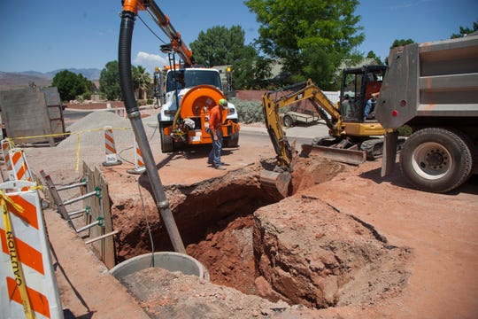 St. George City utility workers inspect an underground pipe submerged in ground water Tuesday, June 18, 2019.