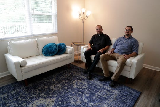 Rev. Dustin Feddon, executive director of Joseph House, and intern Tyler Parker sit in the living room area of Joseph House, a ministry to assist the formerly incarcerated, created by the Diocese of Pensacola-