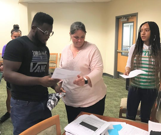 Perspective freshmen Eljin Rhymes (left) of FAMU football and women's basketball Caylan Jones go over their paperwork with athletics financial aid coordinator Lori Goodart during orientation for the Rattler Summer Institute.