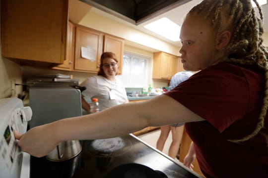 Kennedy Brown, 18, from Crestview, gets help from Megan Hoadley, a Florida State University student, using the oven in the kitchen of FSU's Rotary Scholarship House during Lighthouse of the Big Bend's transition summer camp for students who are visually impaired Tuesday, June 18, 2019.
