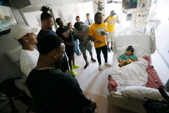 Former UTEP football players Alvin and Aaron Jones visit Valentina Herrera, 8, on Wednesday, June 19, 2019. They were joined by fellow UTEP alumnus Roy Robertson-Harris and NFL players DeShon Elliott, Trevor Davis and Jeff Wilson during the visit to Las Palmas Medical Center. They are in town for the Jones Brothers Youth Football Skills Camp.