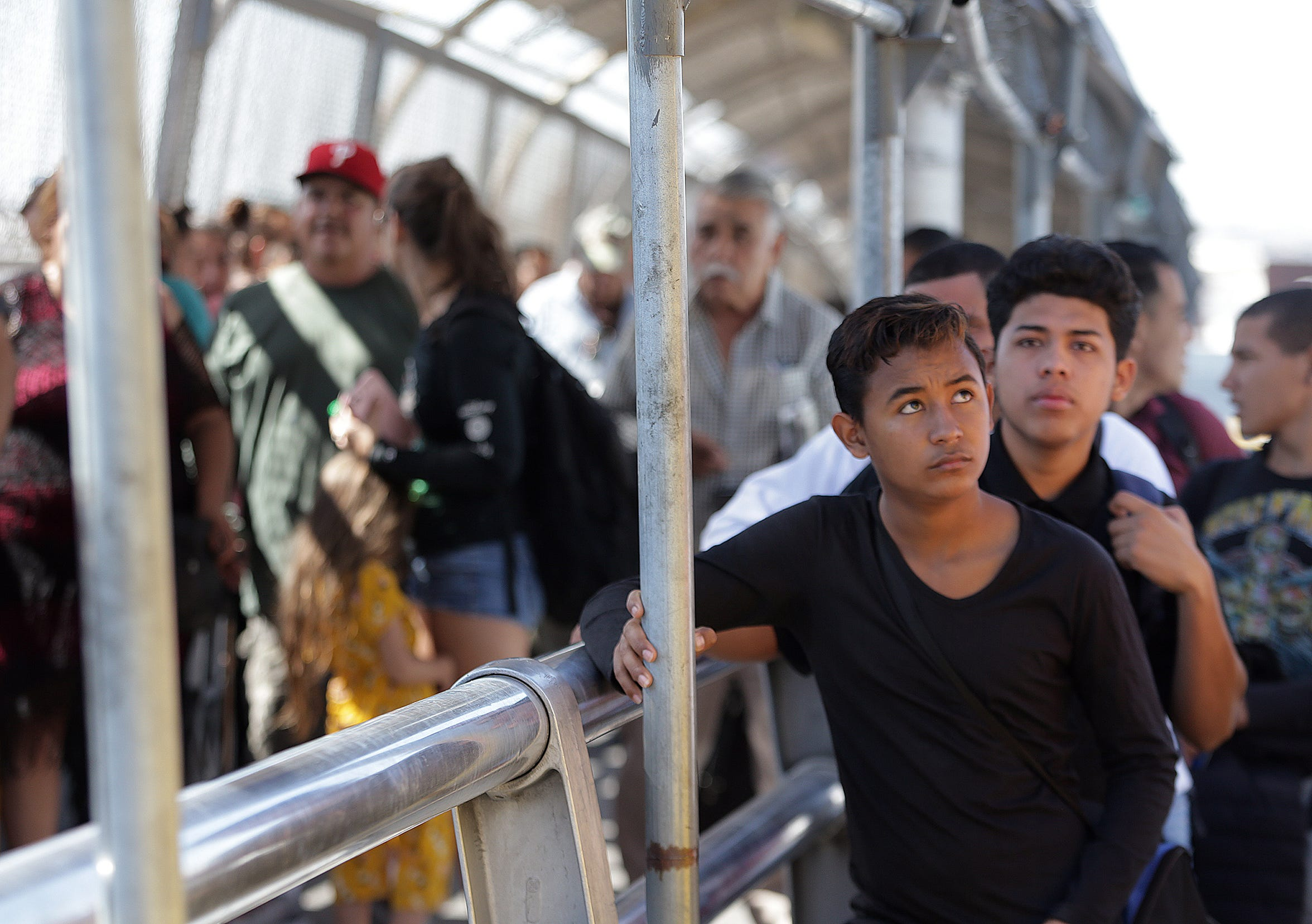Honduran asylum seeker Christian Flores is escorted over the bridge after his number was called in Juarez Tuesday.