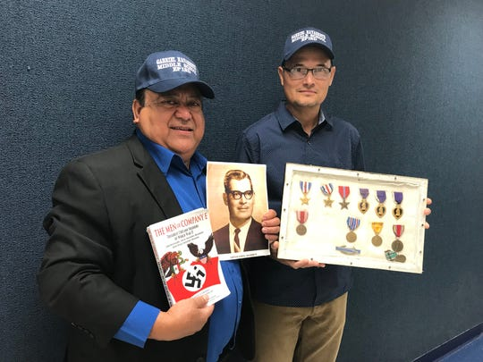 "Arnulfo Hernandez Jr., left, co-author of ""The Men of Company E: Toughest Chicano Soldiers of World War II,"" and Michael Navarrete, Gabriel Navarrete's grandson, pose with the war hero's medals after the El Paso Independent School District board of trustees voted to name a new middle school in honor of the World War II soldier Tuesday, June 18, 2019."