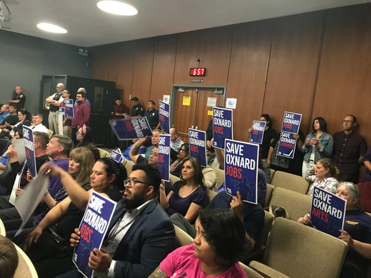 People in the audience at Tuesday's Oxnard City Council meeting hold up signs calling on Oxnard leaders to save some of the proposed budget cuts.  Council adopted a budget on a 6-to-1 vote.