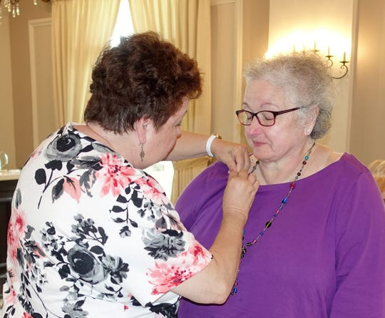 Norene Ritter (left), past president of the Woman's Club of Vineland, pins Judy Fagotti with a special pin for being selected as the club's Woman of the Year.