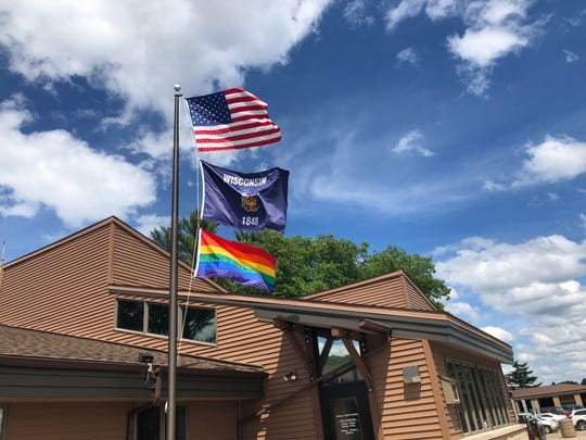 A Pride flag flies below the Wisconsin and American flags at the Rib Mountain Department of Motor Vehicles in Marathon County on June 18.