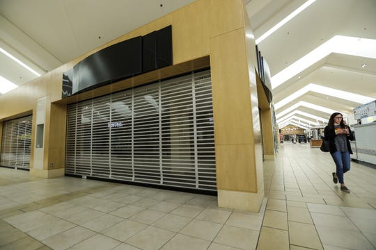 A shopper walks pass an empty store Tuesday, June 18, 2019, at the Wausau Center mall in downtown Wausau, Wis.