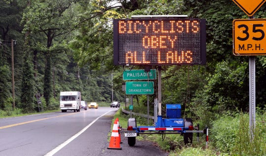 A message board alerts riders of a new Orangetown law that says bicyclists must ride in single file June 19, 2019. The sign is on Rt.9W in Palisades.