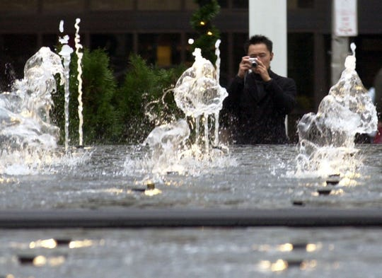 A man takes a photo of the fountain at the corner of Main Street and Mamaroneck Avenue in White Plains on Nov. 11, 2003.