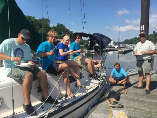 Sea Scouts from Lewes eat breakfast on their boat the day after an engine fire scuttled their long cruise to Baltimore.