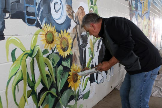 "Pete Cortese, head muralist with Mixdesign, makes sunflowers ""pop"" from a 45-foot by 10-foot mural at the Wisonsin State Fair's lower cattle barn on June 18. The mural will be part of a new interactive exhibit at the State Fair."