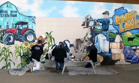 Artists from Mixdesign work on a 450-square-foot mural that is the first element of a new interactive exhibit at the Wisconsin State Fair.