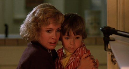 "Karen (Catherine Hicks, left) and son Andy (Alex Vincent) try to survive Chucky's killing spree in the 1988 ""Child's Play."""