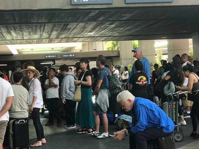 In this photo provided by Leslie Ryan, passengers jam the open air lobby at Terminal 2 at Daniel K. Inouye International Airport in Honolulu, Tuesday, June 18, 2019. Flights were being delayed and hundreds of people were waiting to go through security screening at Honolulu's airport after an active shooter scare.
