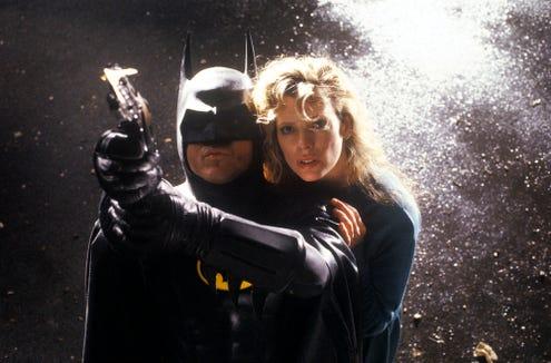 "The Caped Crusader (Michael Keaton) saves Vicki Vale (Kim Basinger) from certain doom in ""Batman."""