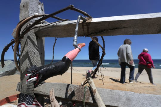 In this May 22, 2019, file photo, three women pass a makeshift memorial at Newcomb Hollow Beach, where a boogie boarder was bitten by a shark in 2018 and later died of his injuries, in Wellfleet, Mass.