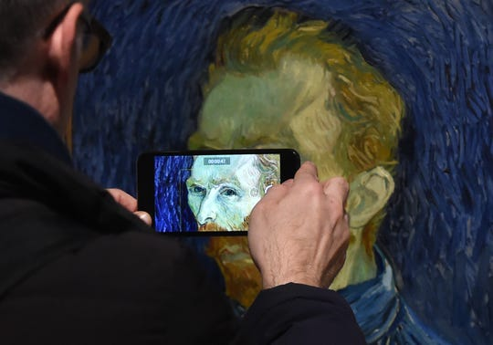 "A man takes a close-up photograph of a self portrait by Vincent van Gogh at the ""EY Exhibition: Van Gogh and Britain,"" which opened at Tate Britain in March 2019 in London."