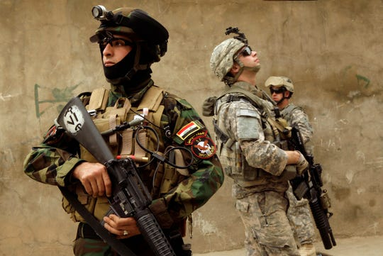 In this March 13, 2009 file photo, an Iraqi Army soldier, left, and U.S. Army soldiers, including Cpl. Jason G. Pautsch, center, from D Co., 1st Combined Arms Battalion, 67th Armor Regiment, stand guard during a joint patrol in Mosul, 360 kilometers (225 miles) northwest of Baghdad, Iraq. Cpl. Pautsch, 20, from Davenport, Iowa, was one of five soldiers killed by a truck bomb on April 10, 2009.