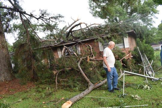 A tree limb lodged in the middle of Mike Hodge's house on Gayven Drive in Ball. Hodge was asleep in his bedroom that didn't get the damage that the center of his house did. Thursday morning storms left a trail of damage in Ball.