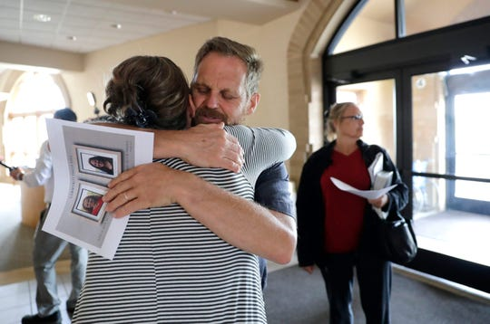Kelly Rousseau holds a flier about his missing wife, 55-year-old Jill Rousseau, and missing daughter, 21-year-old Jordan Rousseau, as he embraces a family friend during a prayer vigil at Calvary Bible Church in Neenah. Kelly Rousseau learned during the prayer vigil that Jill and Jordan were found alive and safe in Madison.