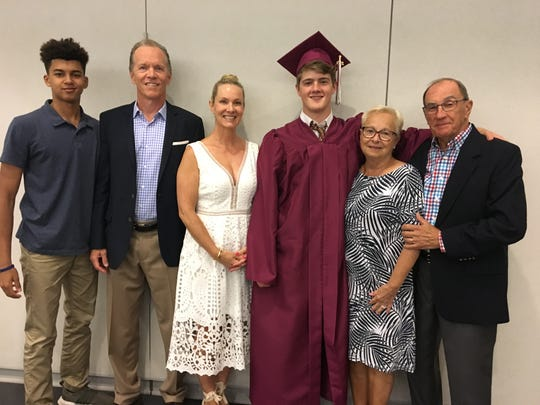 After receiving his diploma, Jackson Croke (center, cap and gown) poses with (from left to right) brother Max, father Jim, mother Patricia and grandparents Joyce and Vito DeMonte.