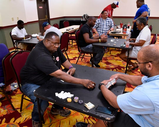 Abilene detective Will Ford reaches across the table to lay a domino before his opponent during Wednesday's tournament at the MCM Elegante Suites June 19, 2019. Ford came from behind to win the tournament, which was part of this week's Police Games.