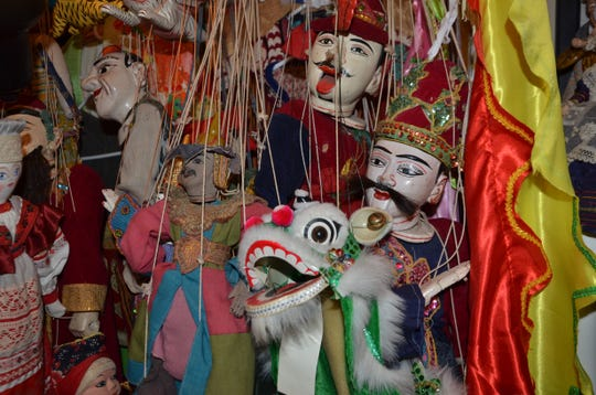 Marionette puppets dangle in the basement of the Holderbaum house in Battle Creek.