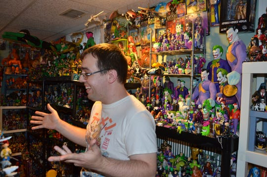 Josh Holderbaum shows off his collection of action figures  in the basement of his home on Woodrow Ave. South in Battle Creek. Holderbaum estimates his collection to be near 10,000 figurines.