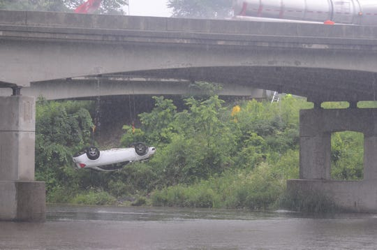 A car that plunged off Interstate 94 is lifted from the edge of the river back to the roadway Thursday morning.