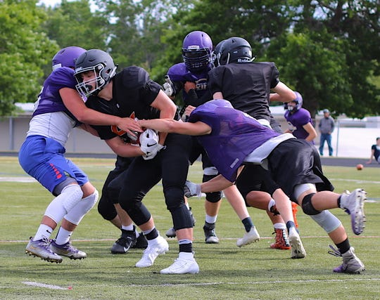 North Kitsap's defense flies to a Central Kitsap ball carrier during Wednesday's scrimmage.