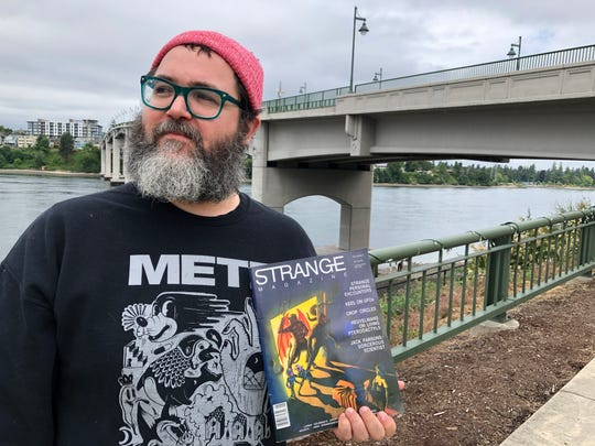 "Garrett Kelly, a self-described ""liminal cartographer,"" holding a copy of Strange Magazine. Kelly has been researching the history of Bremerton's own cryptid, a giant shrimp he affectionately calls ""Shrimpy."""