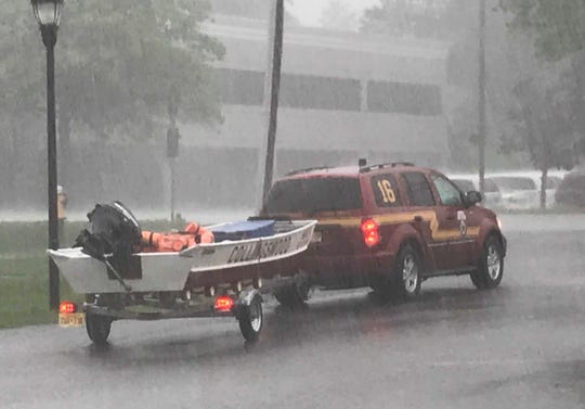 A Collingswood Fire Department boat is stationed outside a Cherry Hill fire station during a downpour Thursday.