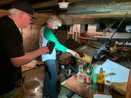 Gloucester City Historical Society President Carol Lynn Carey-Lee and her husband William Lee examine sopping wet artifacts inside the group's museum on King Street on the Delaware River June 20, 2019.