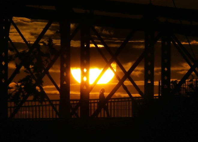 A woman walks across the John A. Roebling Suspension Bridge at sunrise.